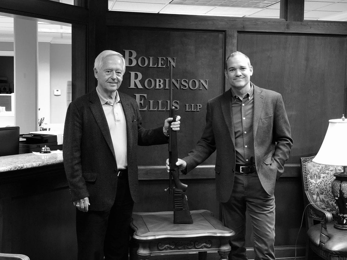 Lawyers Jon Robinson & Chris Ellis holding a Remington 700 Rifle.