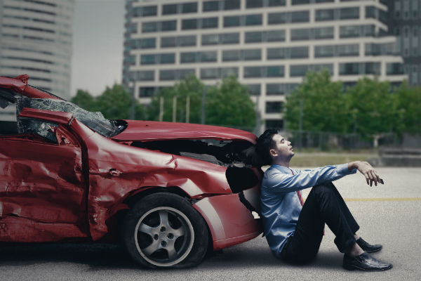 Man sits on the ground in front of a damaged vehicle
