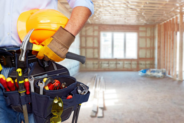 Construction worker wearing tools in house that is being built