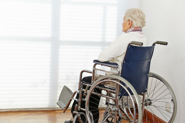 Old woman sitting in wheelchair facing closed window