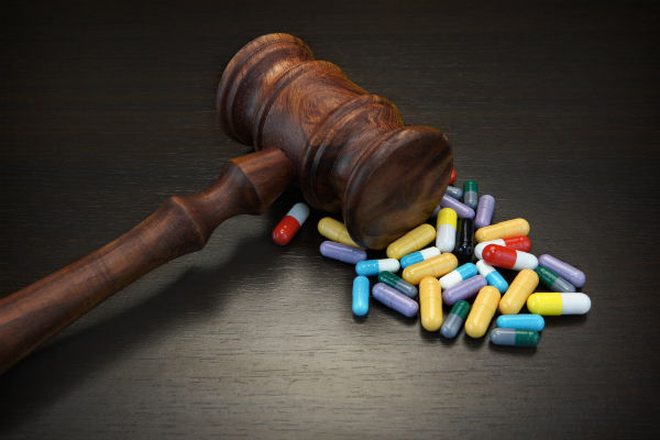 Gavel near a pile of pills