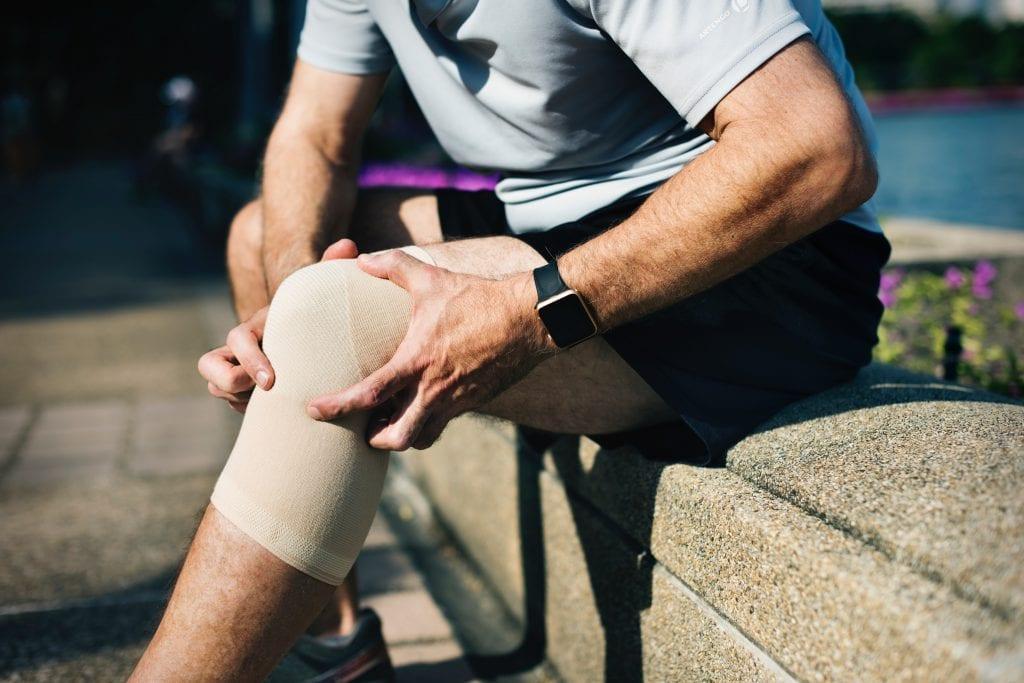 Man holding injured knee